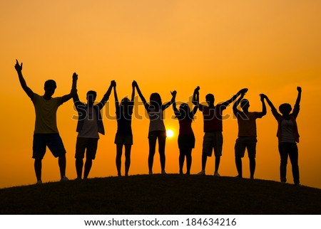 Success: Young People Celebrating at Sunset Royalty-Free Stock Photo #184634216
