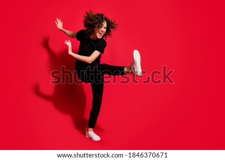 Photo portrait full body view of crazy rebel girl kicking raising leg isolated on vivid red colored background with blank space Royalty-Free Stock Photo #1846370671