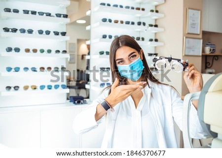 Woman doctor with protective face mask holds in his hands the optical test lenses for testing vision. Medical concept. Ophthalmologist holding try-on tool for lenses selection in the cabinet. Royalty-Free Stock Photo #1846370677