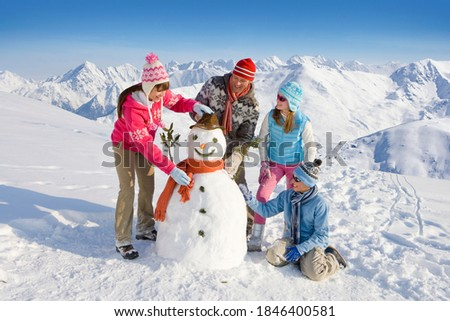 An adorable family having fun while building and decorating a snowman together in front of a magnificent range of snow mountains Royalty-Free Stock Photo #1846400581