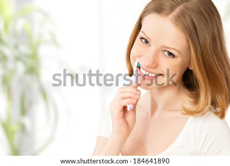 Healthy happy young woman with snow-white smile brushing her teeth with a toothbrush #184641890