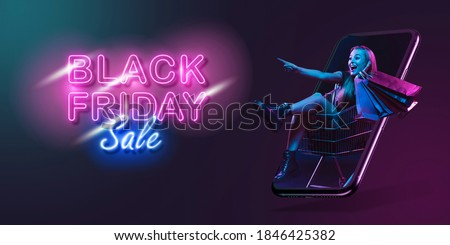 Beautiful woman inviting for shopping right from device screen, black friday, sales concept. Flyer. Cyber monday and online purchases, negative space for ad. Finance and money. Dark neon background. Royalty-Free Stock Photo #1846425382
