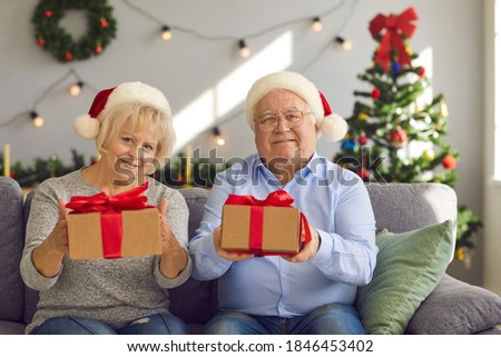 Portrait of happy grandparents in Santa hats sitting on couch at home holding Christmas presents for grandchildren. Video call webcam picture of grandma and grandma giving gift boxes to grandkids