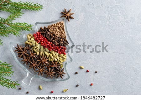 Christmas tree made of variety of spices for christmas and new year festive cooking. Anise stars, cinnamon sticks, pink and black peppers, coriander, cardamon seeds and cloves. Top view. Copy space. #1846482727
