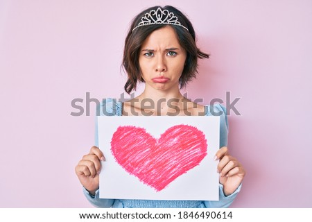 Young beautiful girl wearing princess crown holding heart draw depressed and worry for distress, crying angry and afraid. sad expression.