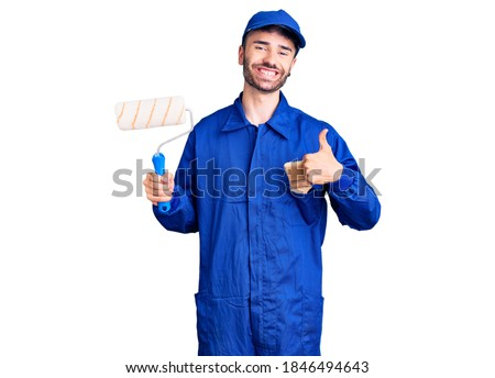Young hispanic man wearing painter uniform holding roller smiling happy and positive, thumb up doing excellent and approval sign
