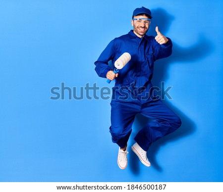 Young handsome hispanic man wearing painter uniform and glasses smiling happy. Jumping with smile on face holding roller doing ok sign with thumb up over isolated blue background