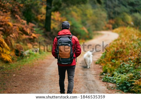 A hiker in a red coat and brown backpack walking with his white dog on a mountain path in spring or fall. Hiker, backpacker in autumn landscape. Mountain and trekking. Concept: Adventure, Art, Travel Royalty-Free Stock Photo #1846535359
