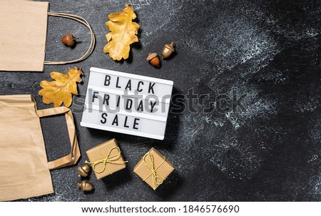 Black Friday Sale banner with text on the lightbox, paper bags, gift boxes and autumn decorations on black rustic background.
