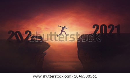 Surreal view, man jumping over a chasm obstacle between old 2020 and new 2021 years. Self overcome, starting a new life. Way to win and success, sunset sky scene. Motivational achieving goals concept. Royalty-Free Stock Photo #1846588561