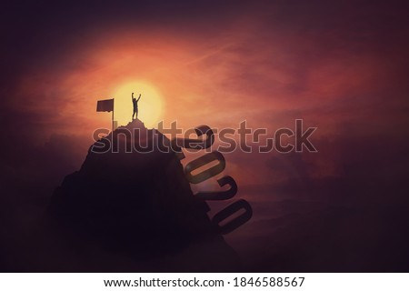 Overcome challenges concept, a courageous man, raising hands up, on the top of the 2020 year mountain, reaching the finish flag, achieving success. Person faced all the obstacles in the past and win. Royalty-Free Stock Photo #1846588567