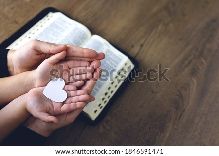 Religious Christian girl praying with her mother indoors. Bible in background. Hads holding white paper heart. Space for text