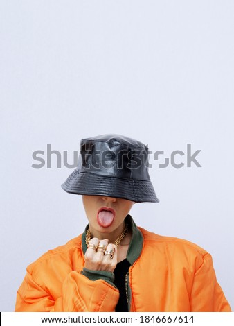 Playful Girl in fashion urban street outfit. Trendy orange bomber jacket and stylish black bucket hat. Fall winter seasons lookbook. Style in details Royalty-Free Stock Photo #1846667614