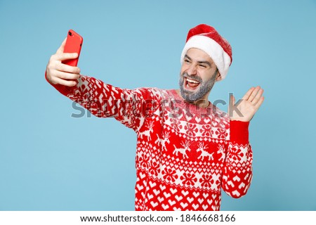 Funny Northern bearded man frozen face in Santa hat Christmas sweater doing selfie shot on mobile phone waving greet with hand isolated on blue background. Happy New Year holiday winter time concept