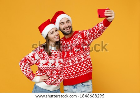 Smiling young Santa couple friends man woman 20s in sweater Christmas hat doing selfie shot on mobile phone isolated on yellow background studio portrait. Happy New Year celebration holiday concept