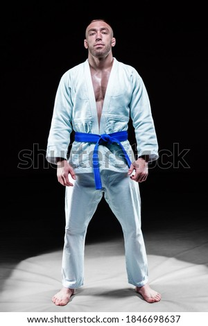 Professional athlete stands in the gym in a kimono with a blue belt. Concept of karate, jiu-jitsu, sambo, judo. Mixed media Royalty-Free Stock Photo #1846698637