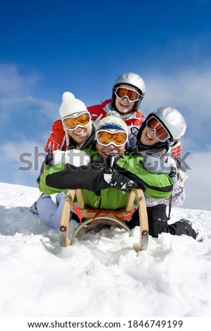 Entire family lying on the sled while sledding down a ski slope on top of a remote mountain