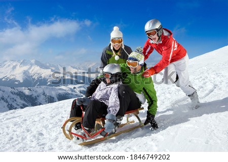 Family enjoying in the snow with Father and son being pushed downhill through the snowy slope while riding on a sled