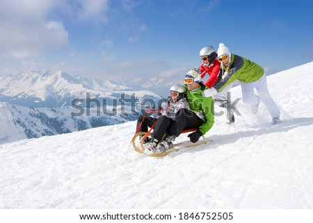An adventurous family having fun in the snow as Father and son being pushed downhill through the snowy slope while riding on a sled