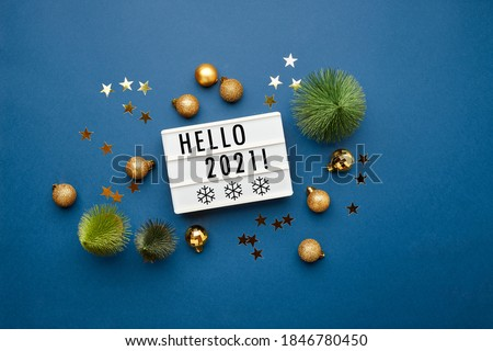 White light box with text Hello 2021, christmas trees, golden christmas balls, snowflakes and stars on blue background. Flat lay, top view, copy space. Christmas frame, New year banner mockup