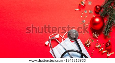 Long wide Christmas banner with festive decorations, medical stethoscope and facial masks on red background. Christmas greeting card for medics concept. Copy space for your text. Royalty-Free Stock Photo #1846813933