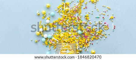 Wide banner Yellow sugar sprinkles grainy on blue background, close-up flat lay Royalty-Free Stock Photo #1846820470