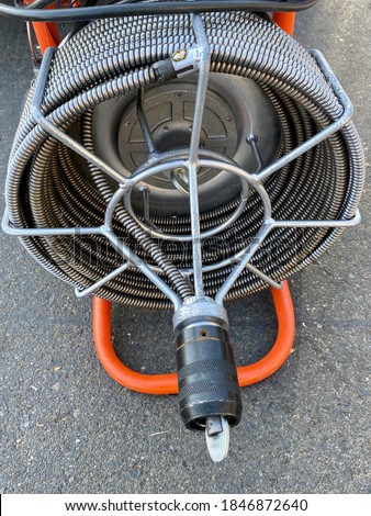Commercial motor powered drain cleaning snake auger closeup.