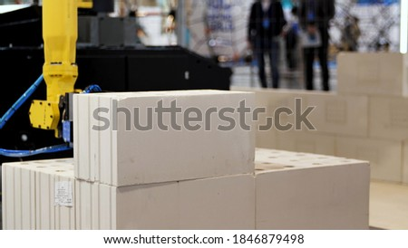 Automatic bricklayer robot working for building a wall. Media. Close up of automated machine presented at the robotic exhibition of technologies in construction industry.