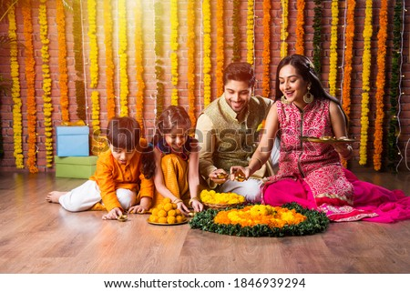 Indian family lighting or arranging oil lamp or diya around flower rangoli on diwali festival night Royalty-Free Stock Photo #1846939294
