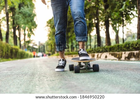 Closeup Asian man leg on surf skate or skate board in outdoor Park when sunrise time over photo blur of unrecognized people running, extreme sport, healthy and exercise.