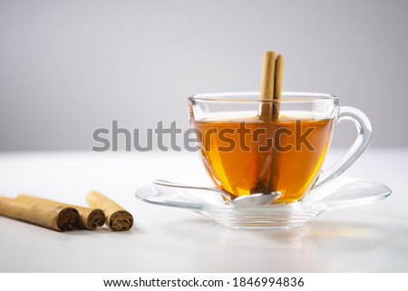 A cup of tea, Cinnamon tea, Cinnamon drink with cinnamon stick on a Tea Bag, leaf on a white background, Spoon, Transparent cup, Ceylon Tea, Sri lanka, Ceylon Cinnamon  #1846994836