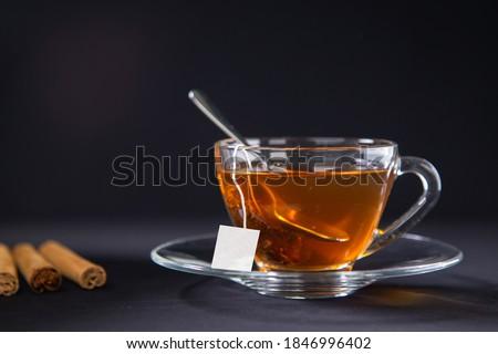 A cup of tea, Cinnamon tea, Cinnamon drink with cinnamon stick on a Tea Bag, leaf on a Black background, Spoon, Transparent cup, Ceylon Tea, Sri lanka, Ceylon Cinnamon  #1846996402