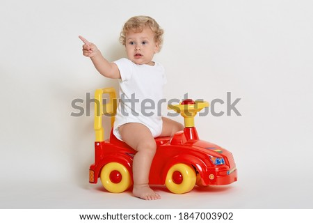 Toddler posing while sitting on toy race car, looking away and indicating with index finger, dresses white bodysuit, baby boy playing indoor, sees something aside, wants to get new toy. Royalty-Free Stock Photo #1847003902