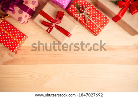 Christmas presents on a wooden table background. Warm colours, copy space.