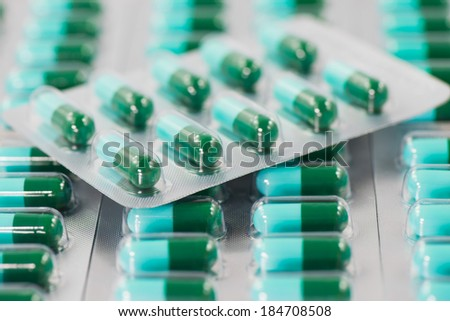 Blue and green capsules of oral medications in transparent strips. #184708508