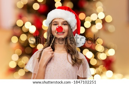 winter holidays and photo booth concept - happy smiling teenage girl in santa helper hat with red nose accessory over christmas tree lights background