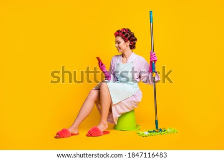 Full size photo of girl wash floor sit bucket use smartphone wear bath robe gloves isolated yellow color background