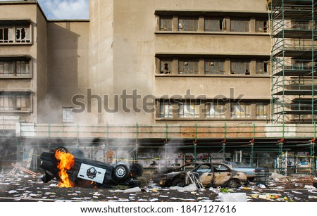 American riots and protests cause vandalism, looting and destruction, riot aftermath concept, upturned police car smashed on fire, broken windows of abandoned building, total anarchy and lawlessness Royalty-Free Stock Photo #1847127616