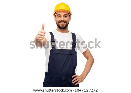 profession, construction and building - happy smiling male worker or builder in yellow helmet and overall showing thumbs up over white background