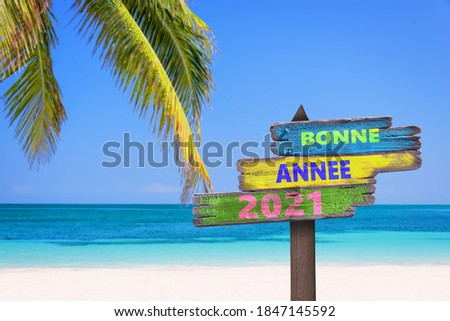Bonne annee 2021, meaning happy new year in French, on direction signs, tropical beach background Royalty-Free Stock Photo #1847145592