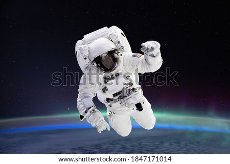Composite image of astronaut floating in space, earth planet in the background -  Elements of this image are furnished by NASA