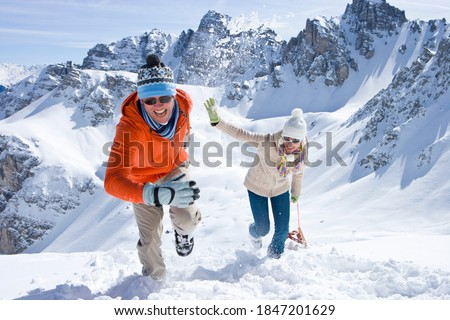 A horizontal front view of a smiling couple playfully climbing up a snow slope while carrying a sled