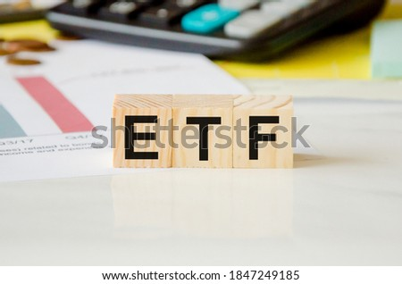 ETF - stock exchange text fund on wooden cubes, cubes lie on a financial chart
