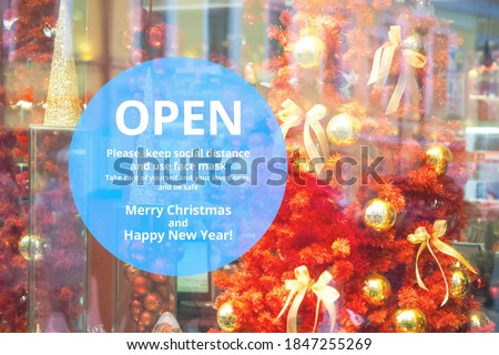 Storefront, shop window, festive christmas decoration. Sign on the front door. Open. Please, keep social distance, use face mask. Take care of yourself, be safe. Merry Christmas and Happy New Year