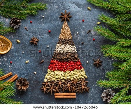 Christmas tree made of variety of spices for christmas and new year festive cooking. Anise stars, cinnamon stick, peppers, coriander, cardamon seeds and cloves. Greeting card design. Christmas concept #1847266846