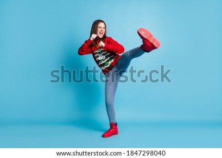 Full length body size photo of funny female student pretending to fight karate keeping one leg up shouting loudly wearing xmas outlook isolated on blue color background Royalty-Free Stock Photo #1847298040