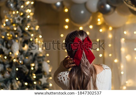 Unrecognizable girl with a bowknot of red ribbon on a xmas background - hairstyle concept. View from the back. Merry Christmas and Happy Holidays. Christmas eve at home Royalty-Free Stock Photo #1847302537