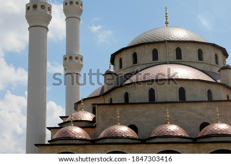 Domes of new mosque with white minarets in a sunbeams. #1847303416