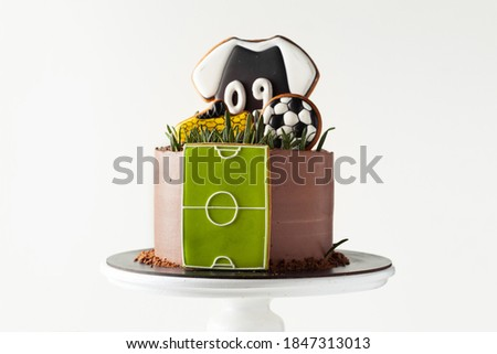 Birthday cake on the football theme on the white background. Gingerbread cookies in a shape of soccer ball, boot and T-shirt.