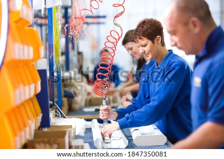 A medium shot of a young female worker working on an aluminum light fittings on the production line with other workers. Royalty-Free Stock Photo #1847350081